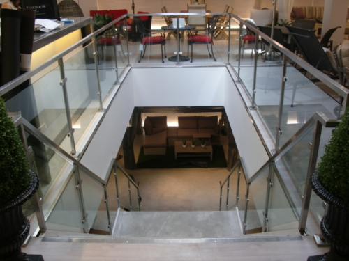 Stainless steel railings between stand offs and glass panels